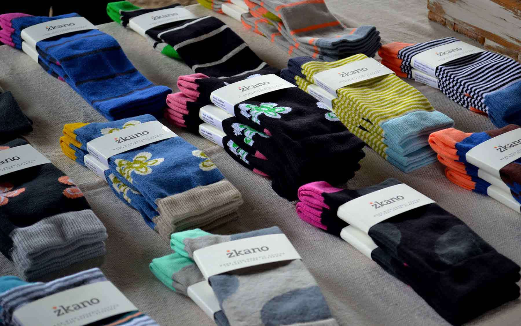 Rows of colorful and patterened sock pairs wrapped in paper Zkano branding
