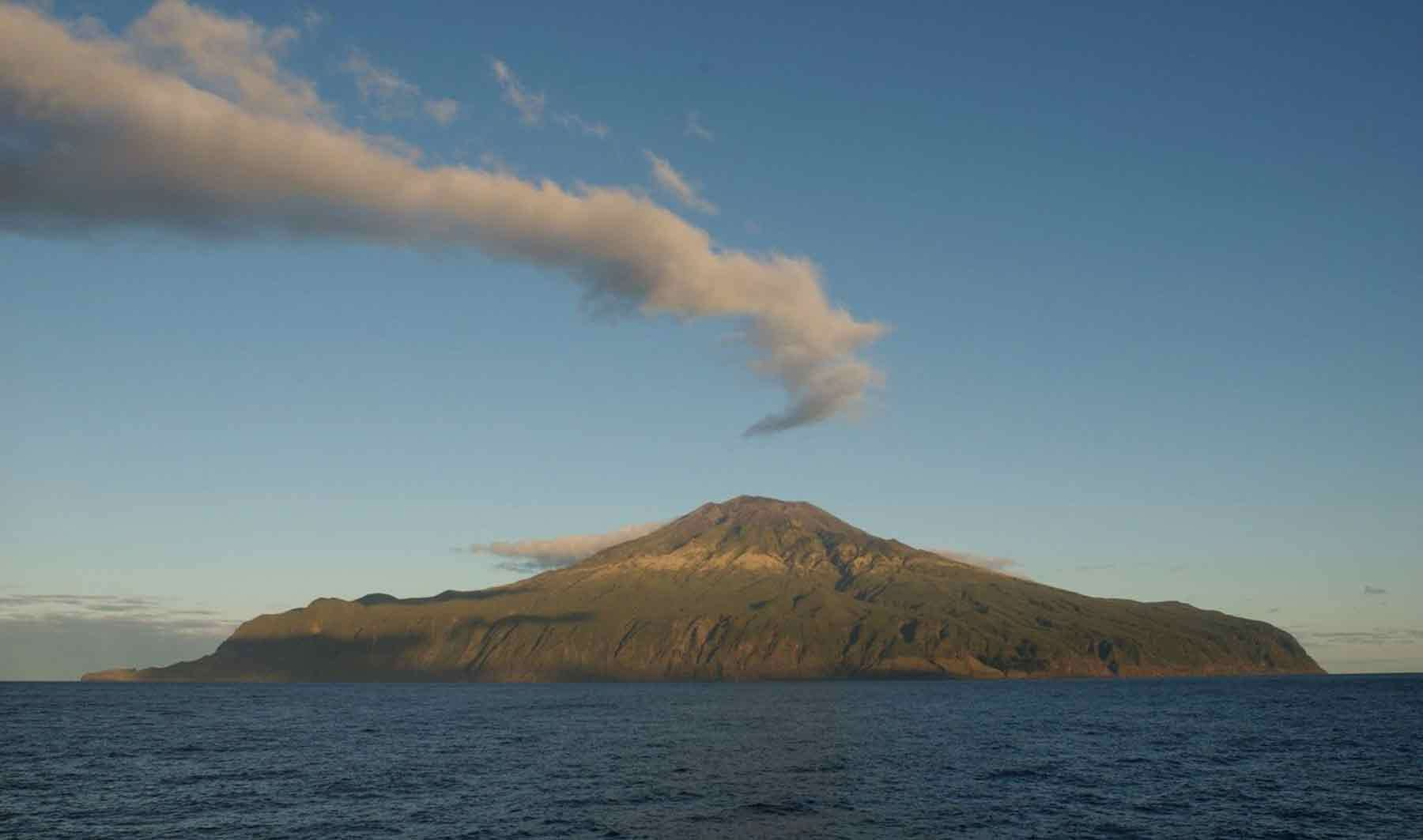 The island of Tristan da Cunha. A volcano shaped island with a drift of clouds above and blue sky and ocean in foreground.