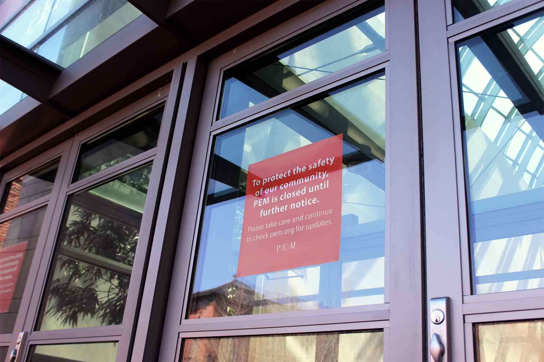 Glass front doors of PEM with sign that says -To protect the safety of our community PEM is closed until further notice