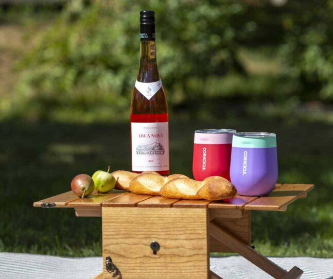 A wicker picnic basket, small wooden table, wine, colers, bread set on a white blanket surrounded by lawn