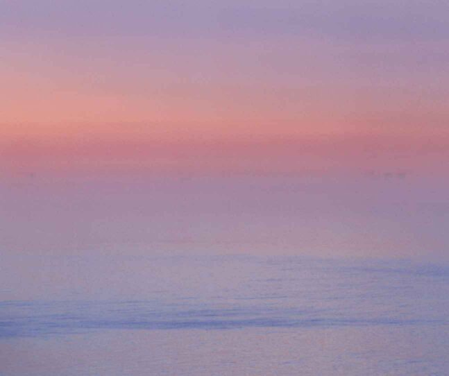 Lavendar, pink, orang glow of a sunrise over ocean