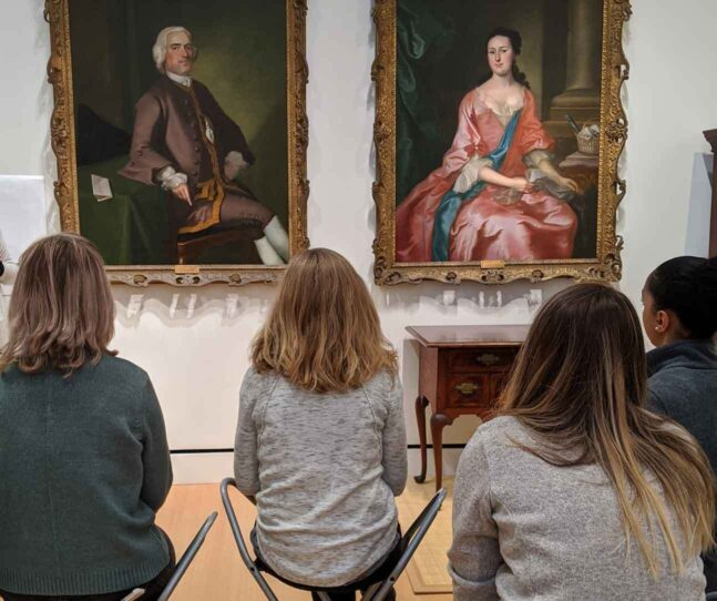 A group of seated women looking at two portrait paintings on thewall in the museum