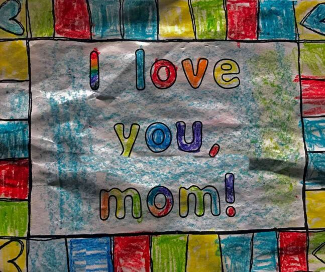 "The word ""I love you, mom!"" hand drawn in many colors with crayon on paper"
