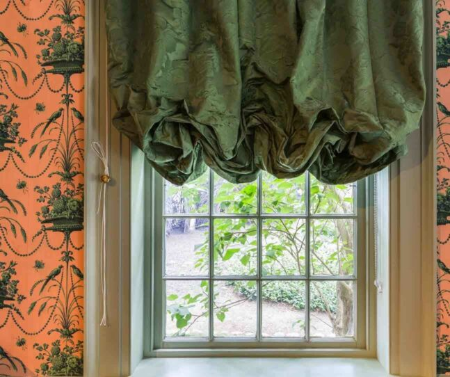 View out a window that has peach and green federal era wallpaper and green silk valance