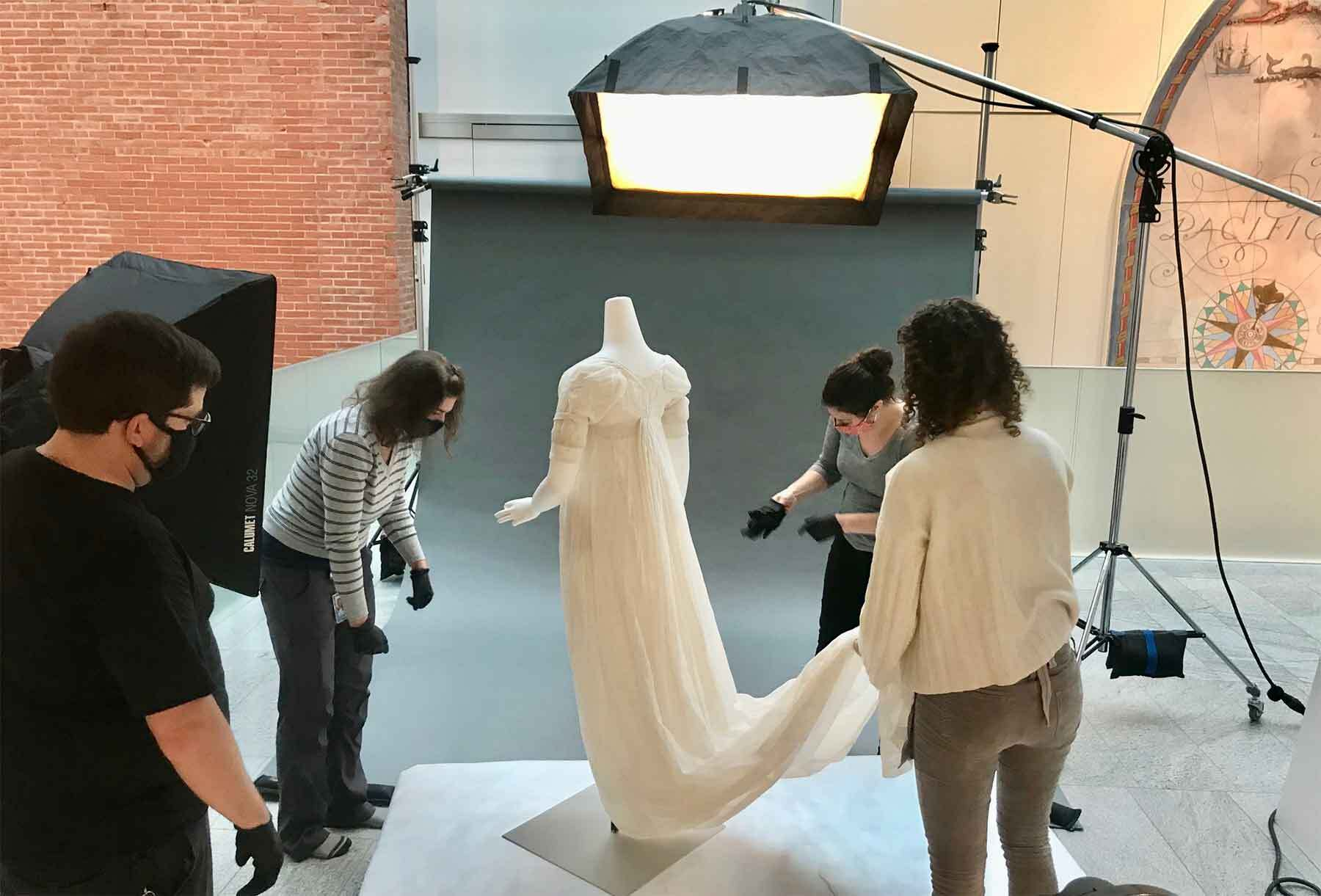 Conservators and preparators prepare a new muslin dress to be installed in the gallery.