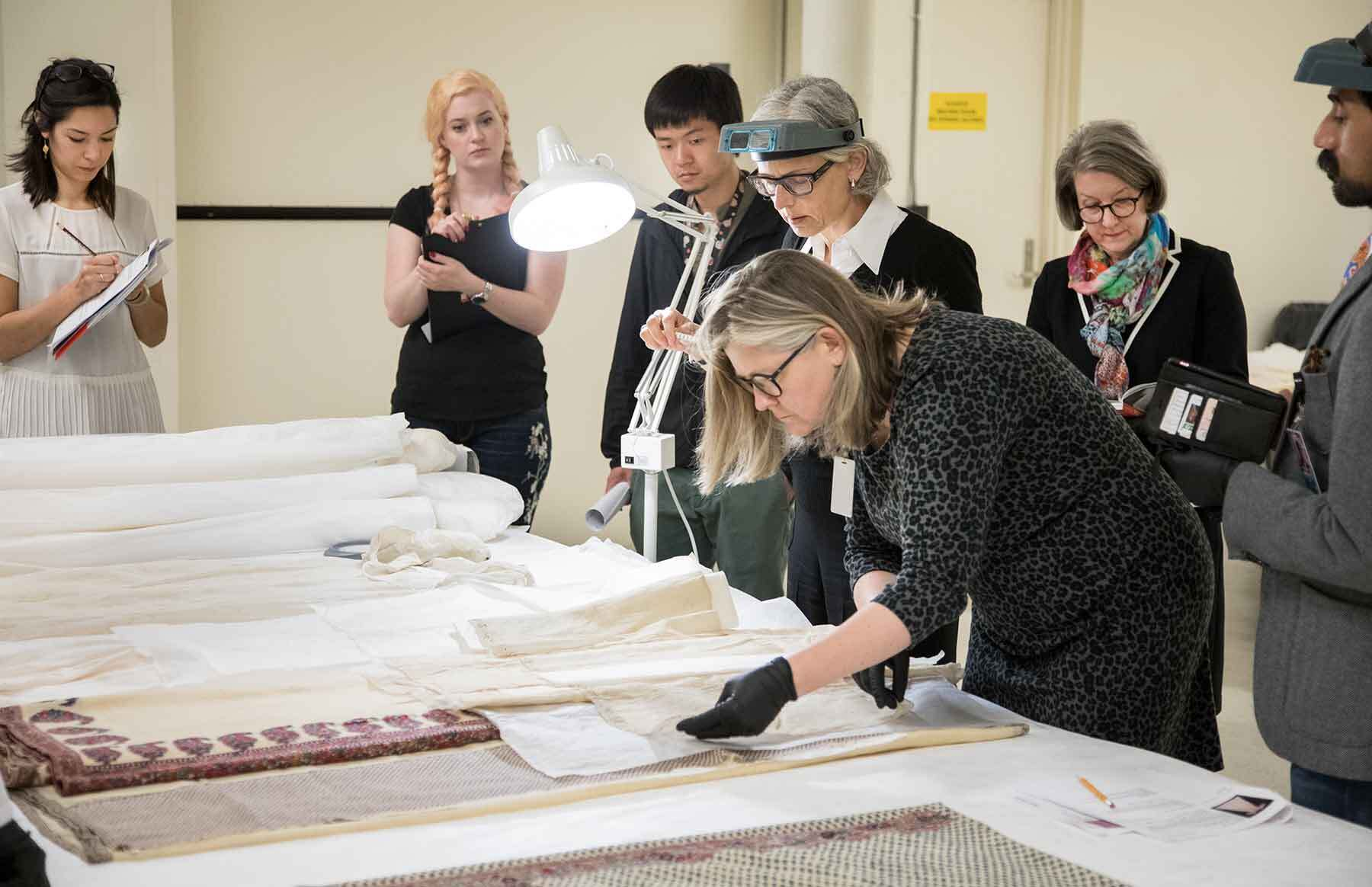 Curators reviewing Indian muslin dresses and Kashmiri shawls with visiting scholars and conservators.
