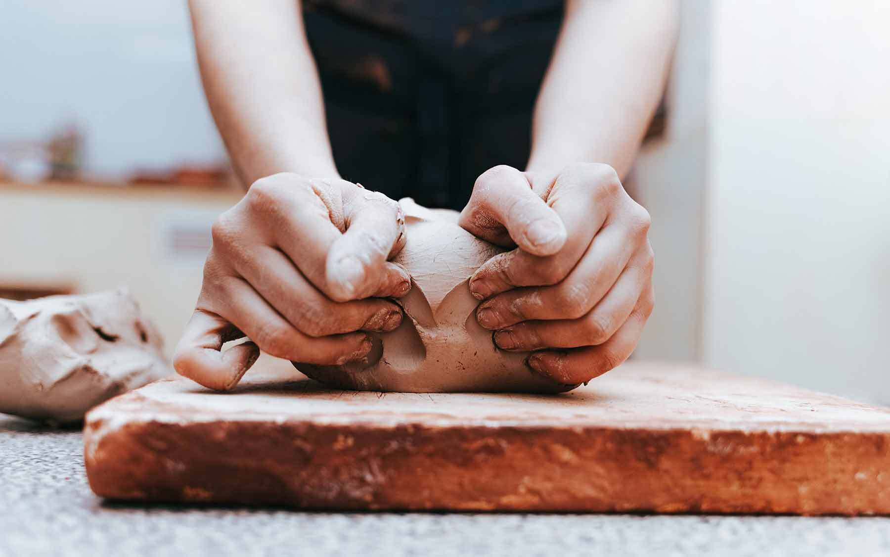 Hands shapoing clay on a table