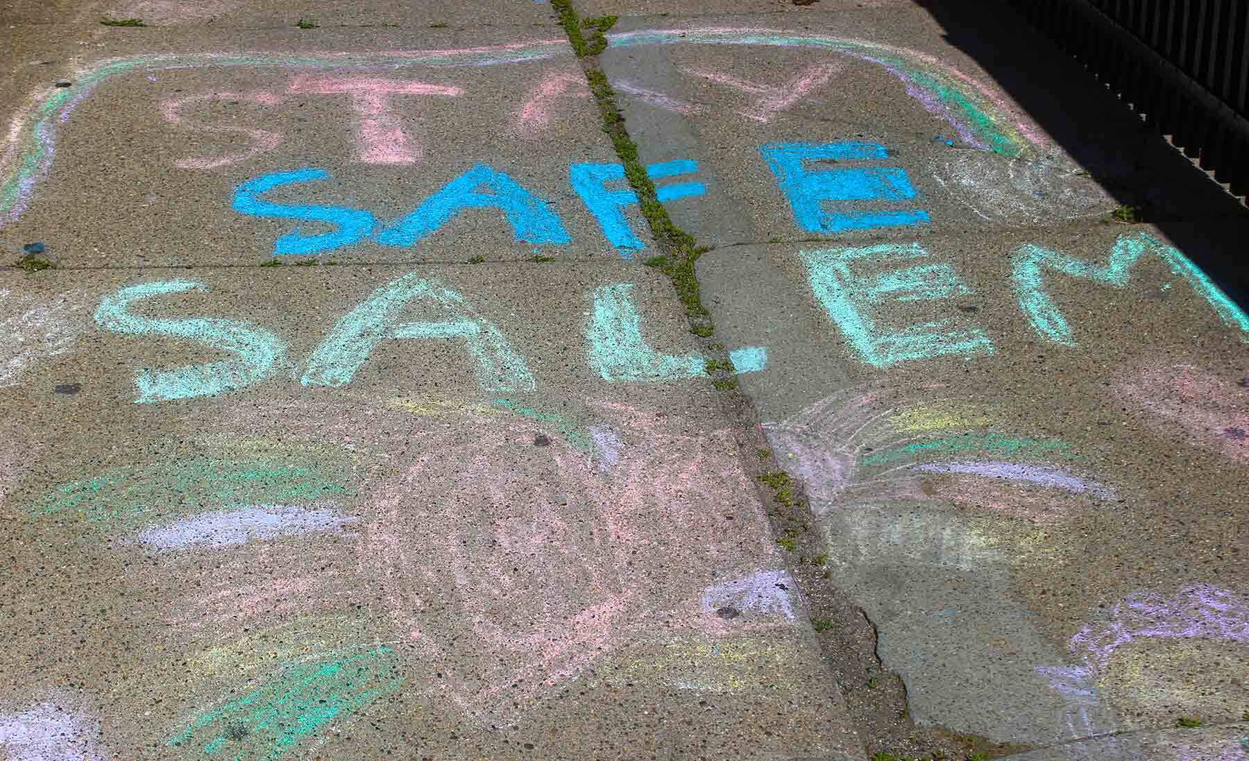 Chalk drawn on grey pavement that says Stay Safe Salem