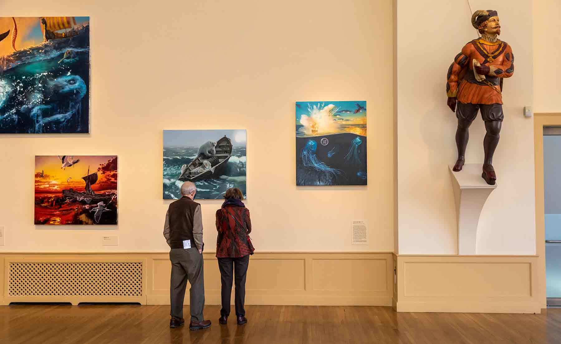 Two people looking at paintings in East India Marine Hall