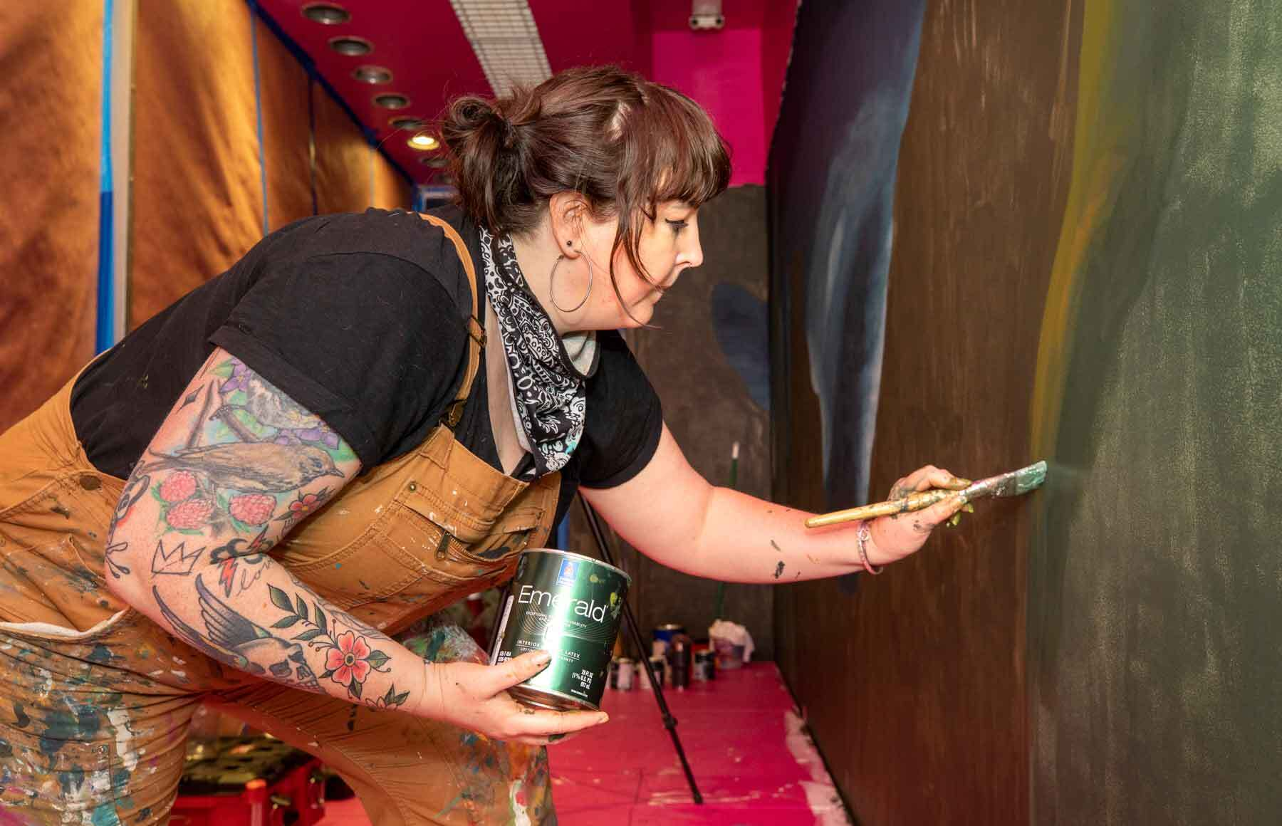 A woman painting a wall.