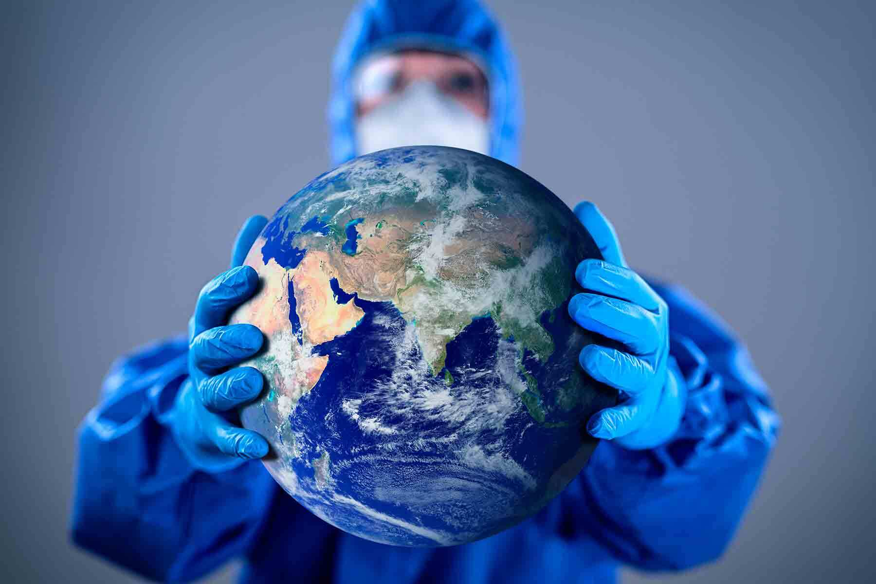 a person wearing blue hazmat outfit, blue gloves and a mask is holding a globe earth.
