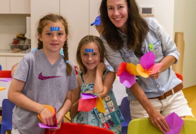A Mother and 2 young girls smiling, holding pink and yellow paper origami creations. They each have a blue PEM sticker on thier foreheads.