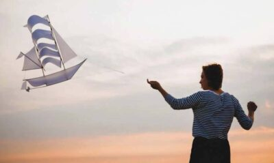 A woman flys a white paper cu ship kite against a cloudy and orange sky