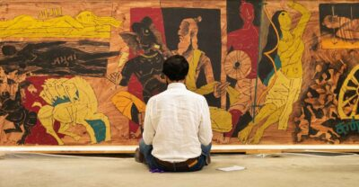 A man in a white shirt is seated on the floor, back to viewer, looking at a large painting of gold, red, brown figures and horses