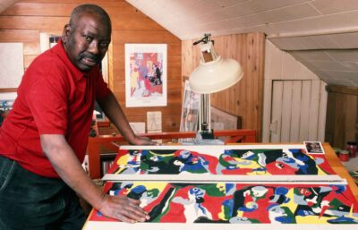 Jacob Lawrence wearing a red shirt stands over a table painting laid on it