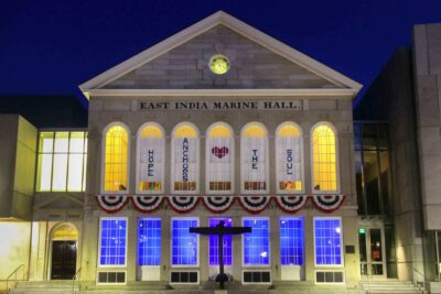 "A night time view of a lit up East India Marine Hall with a banner in the upper windows that says ""Hope anchors the soul""."