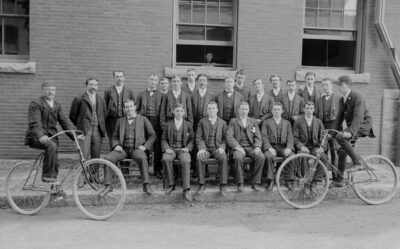 An old photograph of men seated in two rows in front of a brick building. Two men in front are on vintage bicycles and all of the men are dressed in suits.