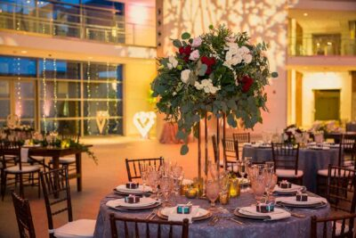 Tall floral vase and tables set for a wedding reception