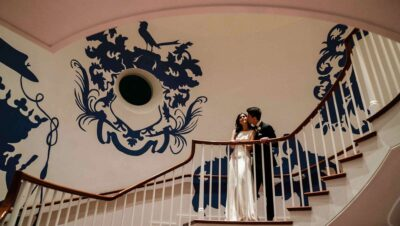 A bride and groom pose on a spiral staircase with intricate blue armor paintings stenciled on the white wall behind them