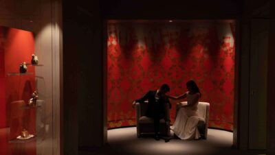 A bride and groom seated in a dark red room with gold stenciled wallpaper