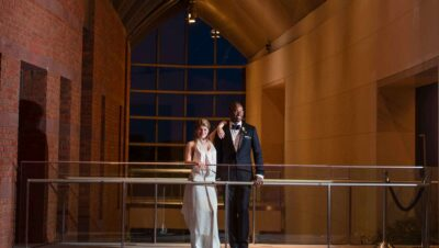 A bride and groom standing on an open walkway with glass railing in the atrium