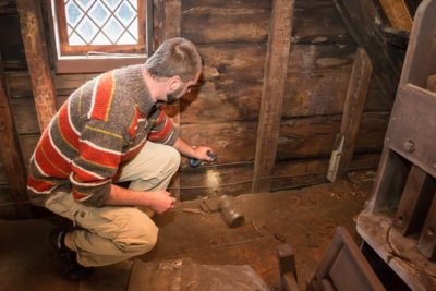 Steven Mallory shining a light on the historic structure of the Ward House. Photo credit Allison White.