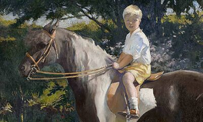 A young boy wearing a white shirt and yellow shorts sits atop a brown and white pony