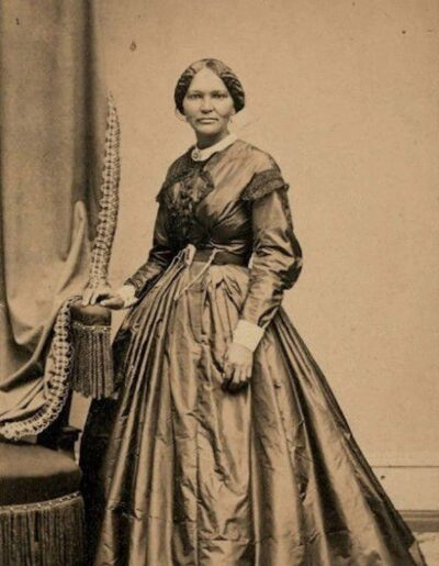 A sepia toned image of Elizabeth Keckley, standing next to draped fabric wearing a dress