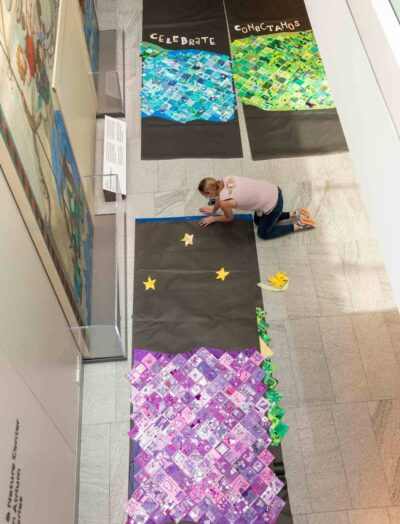 A teacher works to assemble the multi-paneled design at PEM.