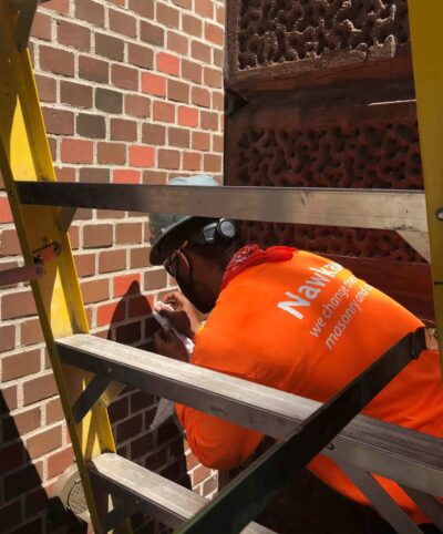 A kneeling man wearing a hard hat next to a ladder is coloring bricks by hand on a brick wall