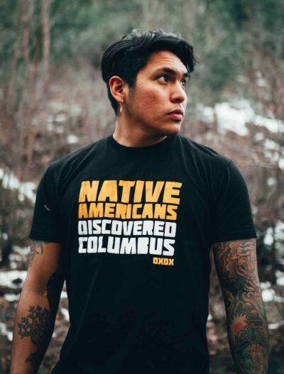 Man wearing a black t-shirt that says, Native Americans Discovered Columbus