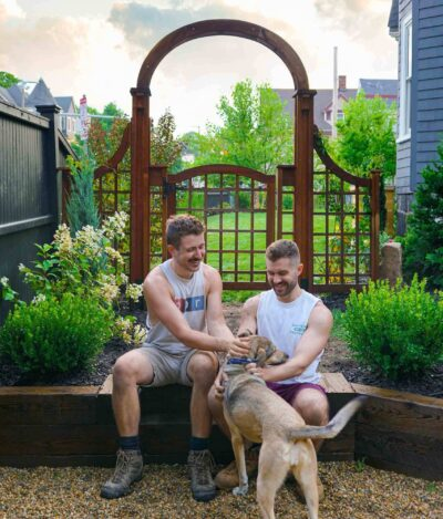 Steven and David with their dog outside in the garden with a wooden gate behind.