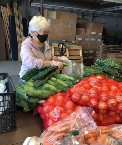 A volunteer packing produce in the warmer months. Photo by Jennifer Percy.