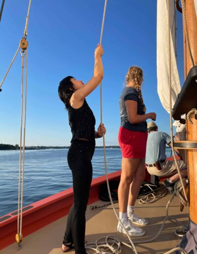 Staff member Melissa Woods helps the crew hoist the sails. Photo by Kathy Tarantola