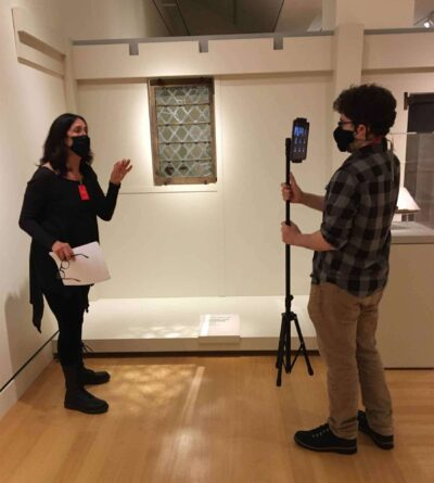 A woman being filmed in a galery space