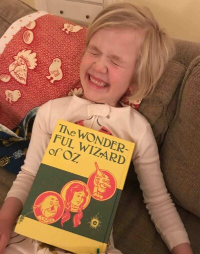 A young girl laughing with The Wizard of Oz book