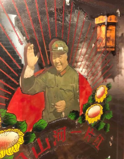 Detail of a 20th century Chinese reverse glass portrait of Chairman Mao with a reflection of a reverse glass painted lantern in the background