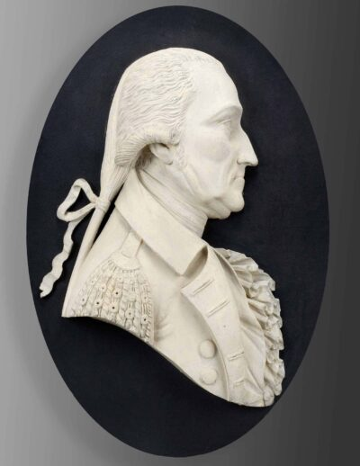 Portrait of George Washington. Carved 1805. Wood, paint. White carving in an oval on a black background.