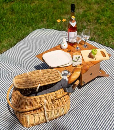 A wicker picnic basket, small wooden table, wine, glasses, pwhite plates, coolers, bread set on a white blanket surrounded by lawn