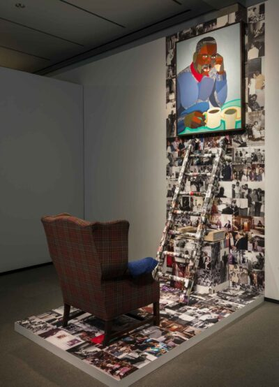 A chair, a wall collage with a ladder and a painting hung on it
