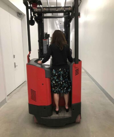 A woman standing on a forklift machine driving away from viewer down a hallway