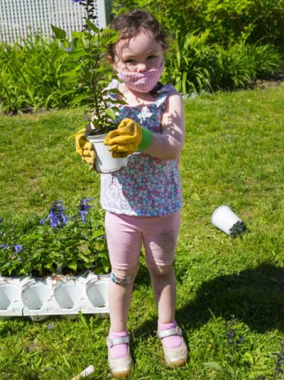 A young girl wearing yellow gloves holds up a blue flowering plant in a white pot