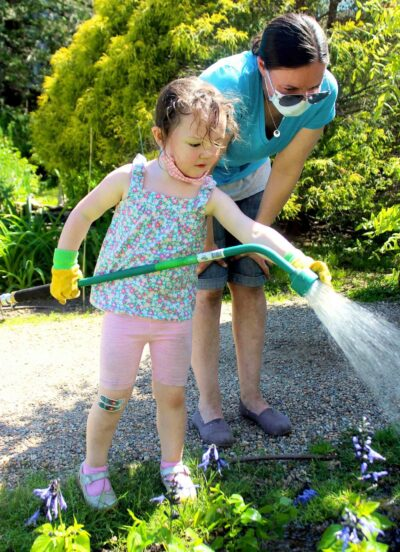 A young girl uses a hose to water the pnewly planted plants while her mom watches.