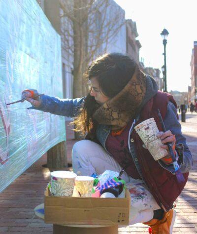 A woman paints a light blue banner outside the museum