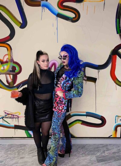 A woman in a black dress standing with another with blue hair and a multi-colored leopard skin suit, in front of a spraypainted wall.