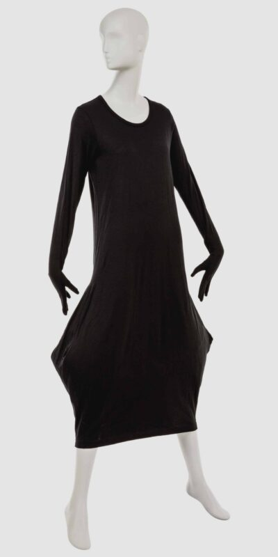A mannequin wearing a straight black dress that points out at the knees and then points back in towards the lower legs