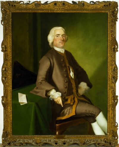 Gold framed painting of a seated man with white hair, wearing a brown suit with knee length trousers, white shirt with frilled cuffs and white stockings.