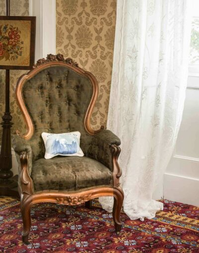 A green apolstered chair with a pillow in a room with lace curtains and gold wallpaper. Interior of the Ropes Mansion