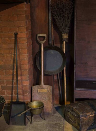 A broom and fireplace tools rest against a brick wall in the Interior of the John Ward House