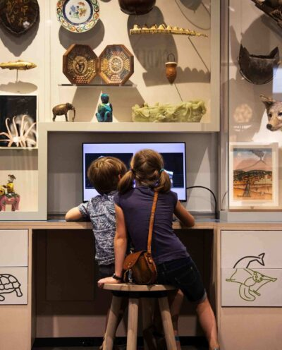Two young children sitting on a stool look at a big computer desktop screen in a room witha artifacts on the wall